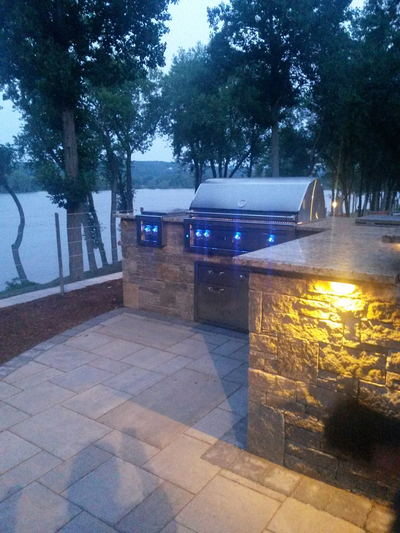 Outdoor Landscape Lighting illuminates a Natural Stone Outdoor Kitchen by Bahler Brothers in Cromwell, CT