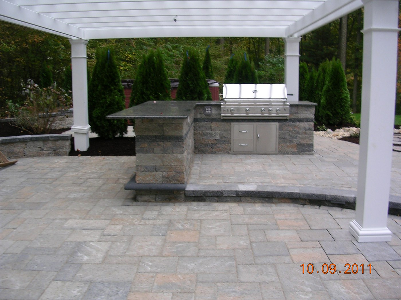Outdoor Kitchen and Bar with Stainless Steel Grill and Pergola set on a Paver Patio by Bahler Brothers in Hebron, CT