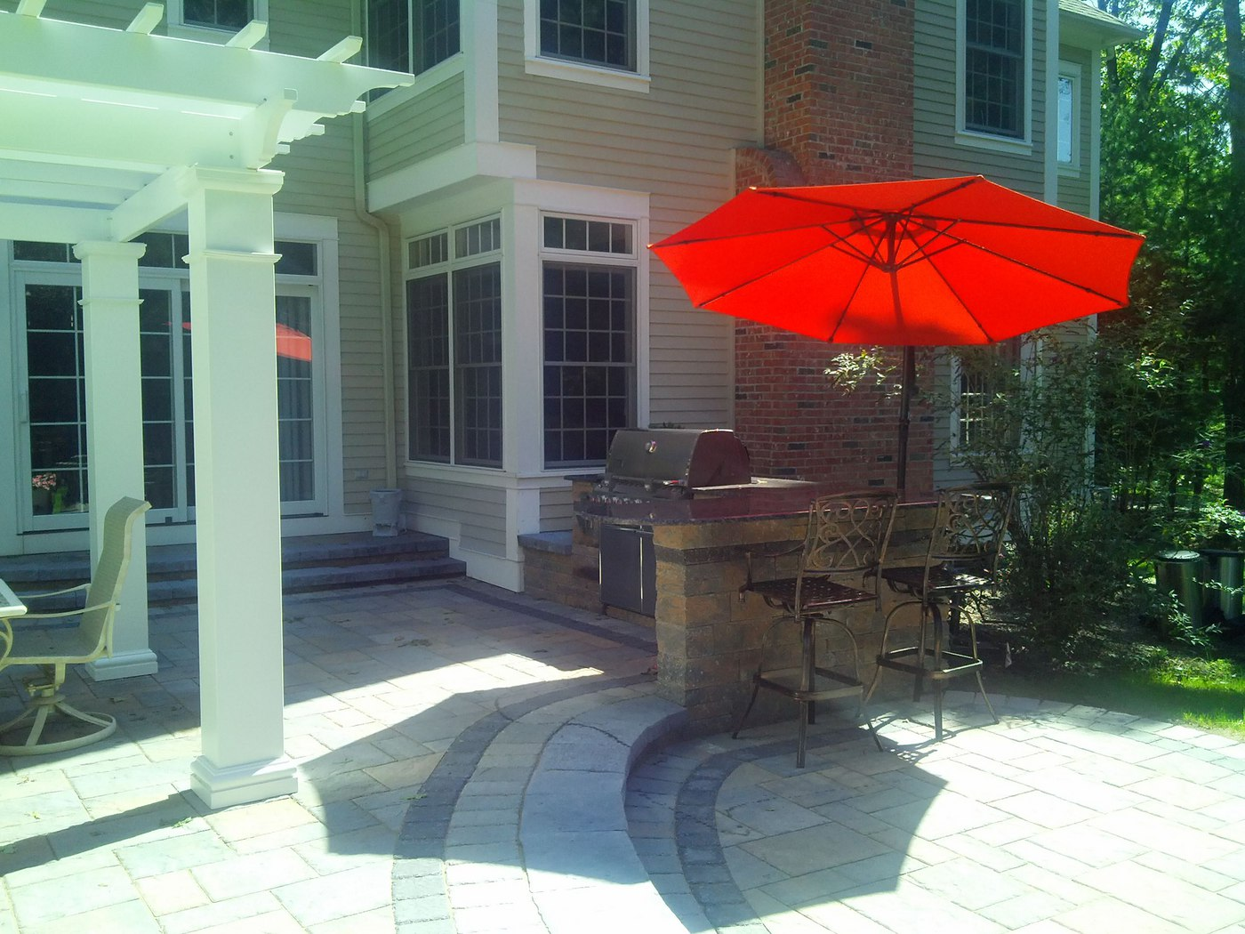 Outdoor Kitchen and Bar with Stainless Steel Webber Grill on Paver Patio with Pergola by Bahler Brothers in Avon,CT