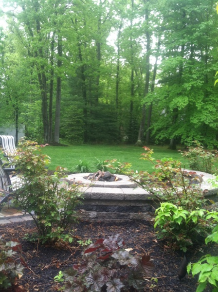A gas fire pit sits on a paver patio surrounded by a sitting wall created by Bahler Brothers in Farmington, CT