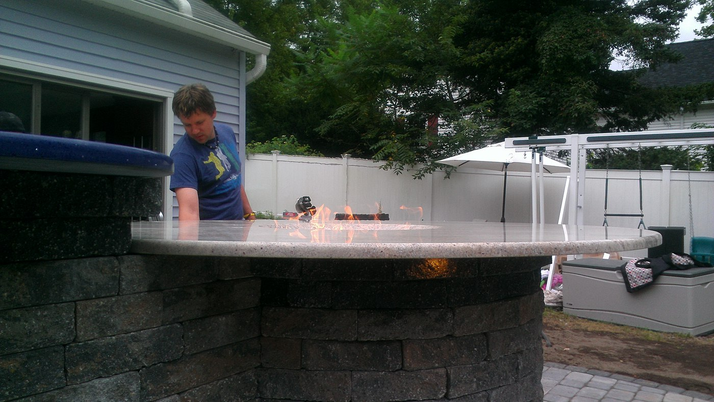 A gas fire table doubles as a bar in an outdoor kitchen built by Bahler Brothers in Glastonbury CT