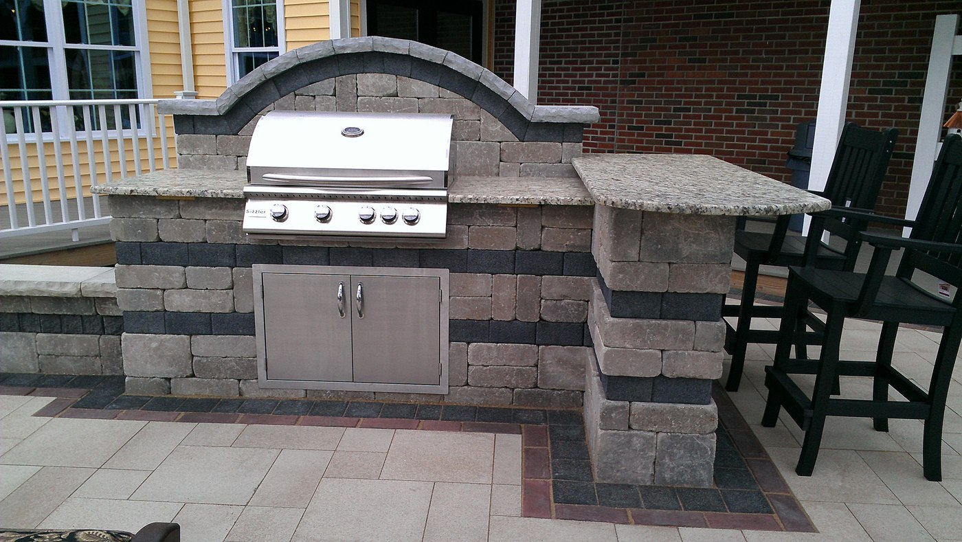 Outdoor Kitchen and Bar with Stainless steel grill and doors on a paver patio designed and built by Bahler Brothers in Ellington, CT