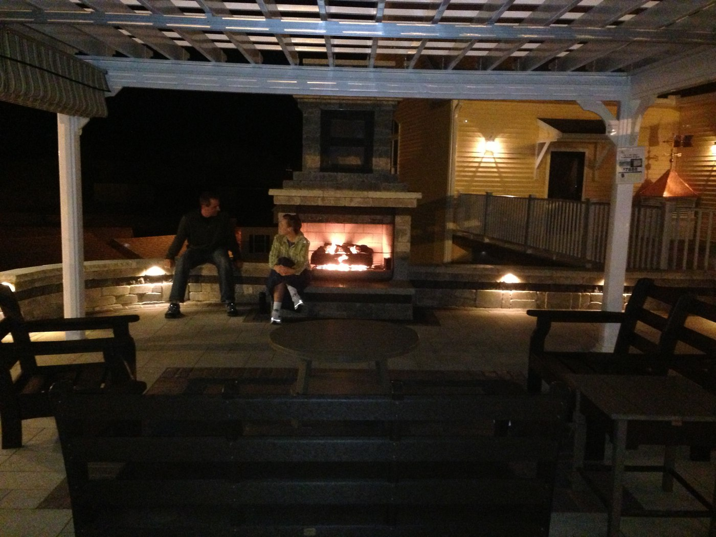 An outdoor gas fire place surrounded by landscape lighting and built by Bahler Brothers burns brightly on a cool evening at Kloter Farms in Ellington, CT