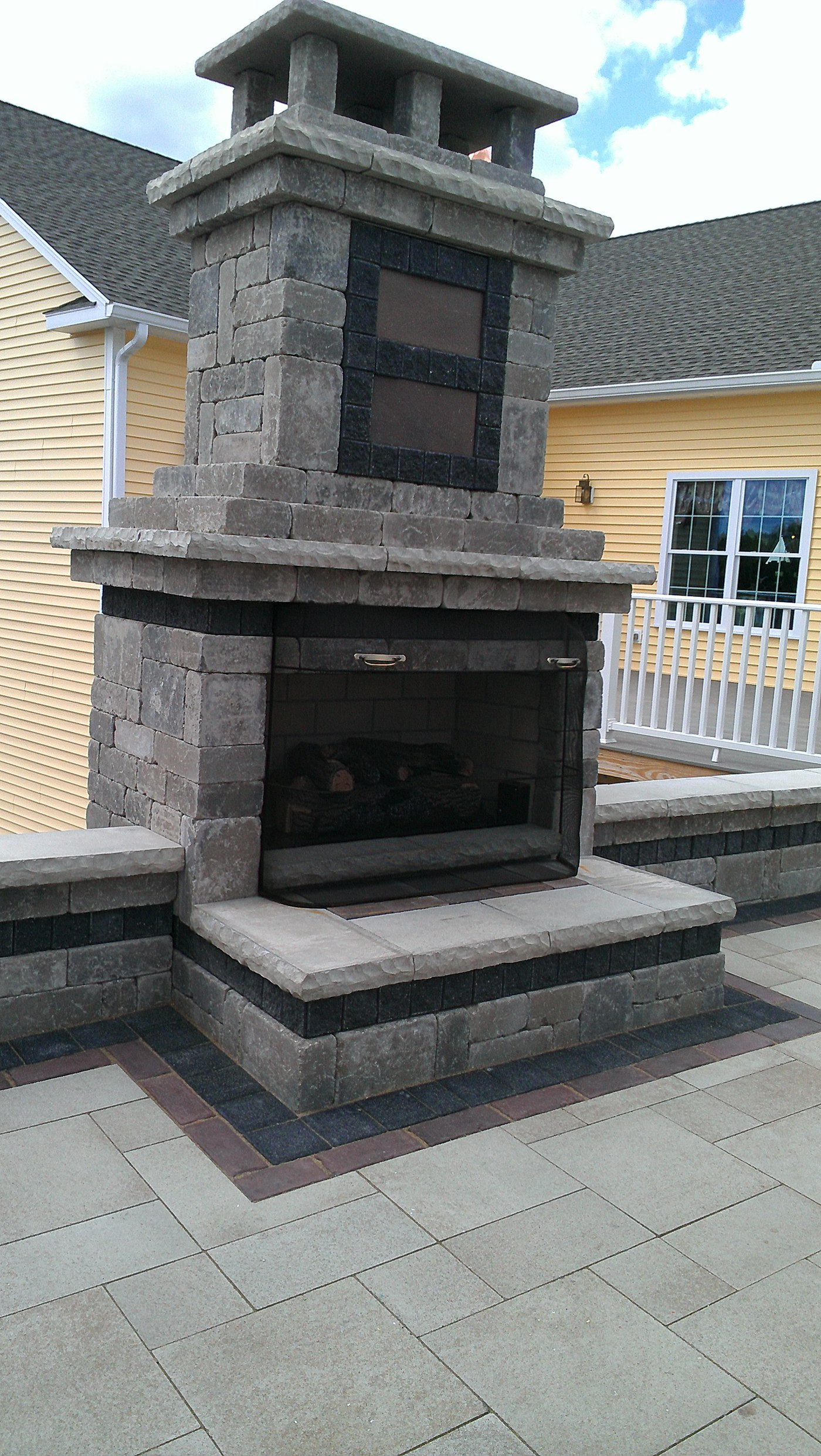 An outdoor gas fire place built by Bahler Brothers sits flanked by Sitting walls on a paver patio in Ellington CT