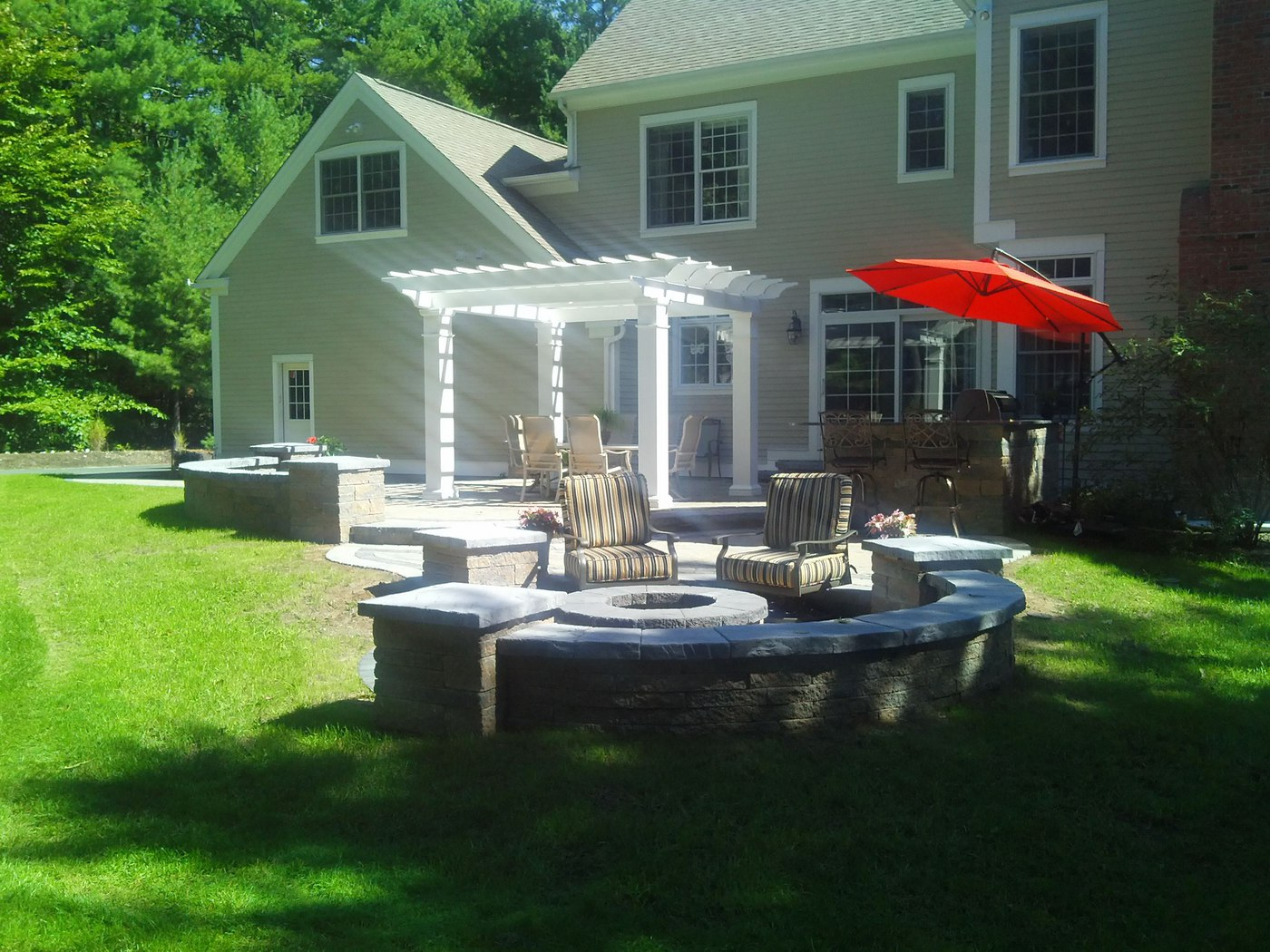 A wood burning fire pit sits on a paver patio surrounded by a sitting wall built by Bahler Brothers in Avon, CT