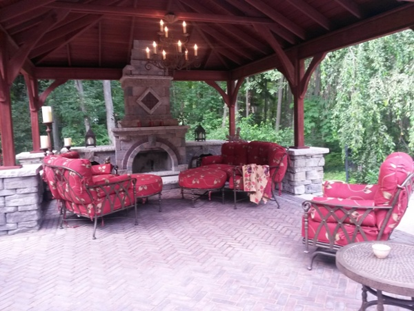 An outdoor fire place covered by a pavilion from Kloter Farms sits on a patio designed and built by Bahler Brothers in Farmington, CT