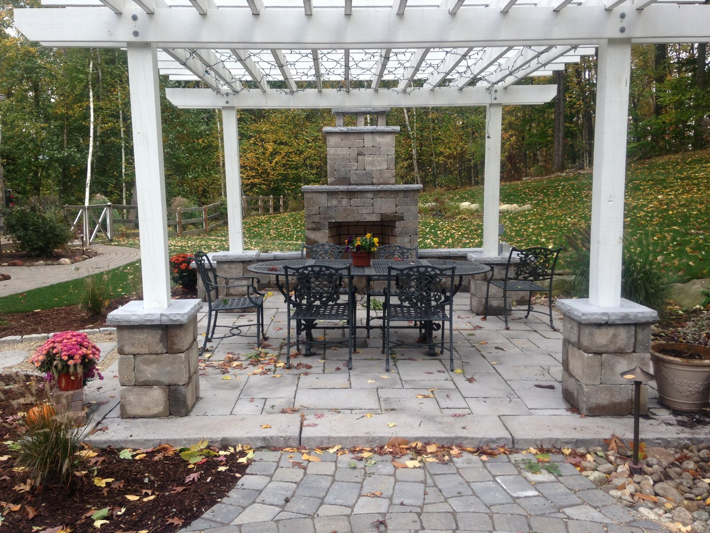 An outdoor fire place built by Bahler Brothers sits on a paver patio with a pergola in South Windsor, CT