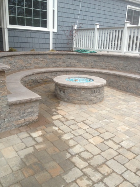 A gas fire pit sits on a paver patio surrounded by a sitting bench built by Bahler Brothers in West Hartford, CT