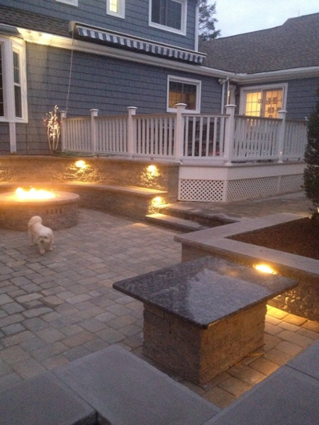 A gas fire pit on a paver patio burns brightly surrounded by landscape lighting designed and installed by Bahler Brothers in West Hartford, CT