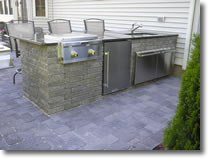 A fully equipped kitchen with a sink, grill, refrigerator, and cabinet space.