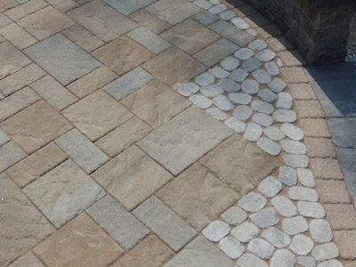 A Side By Side Comparison Of Stamped Concrete And Pavers