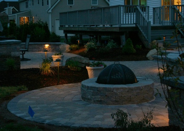 A patio with a fire pit and night lighting.