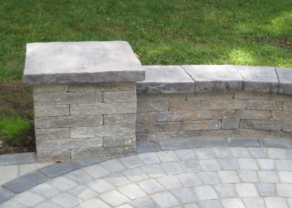 A small sitting wall and pillar to add a vertical element to a simple patio.