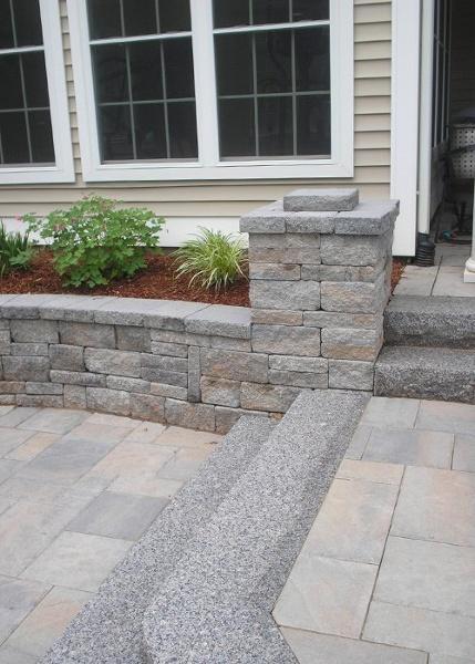 A sitting wall to create space for a planting bed.