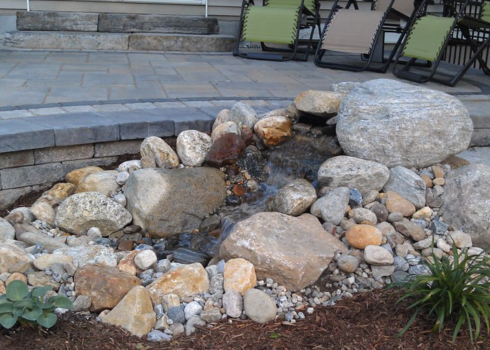 small pondless water feature beside a raised patio in Ellington, CT by Bahler Brothers