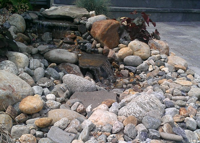 small water feature beside a patio in Ellington, CT. Installed by Bahler Brothers