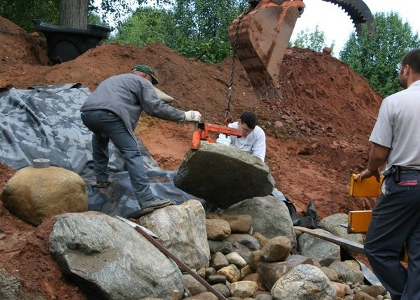 Bahler Brothers is setting the key spillway stone of a large pondless water feature in Somers, CT