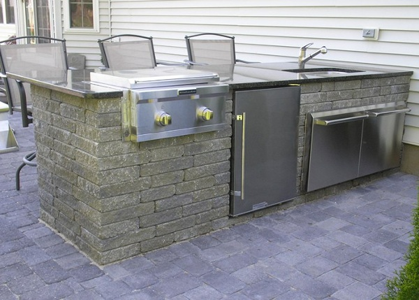 An outdoor kitchen with a stove, refrigerator, sink, and doors for storage. It also has a polished granite counter top.