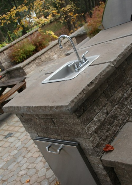 A sink as an added feature in an outdoor kitchen.
