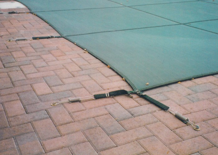 The pins of a winter tension cover for a pool are embedded directly into the pavers of the pool deck. Installed by Bahler Brothers