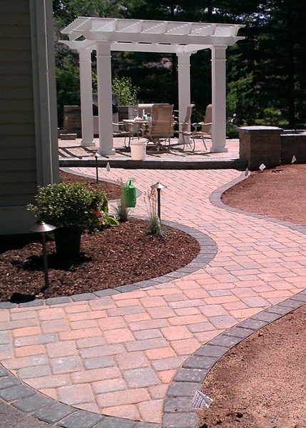 Walkway to a backyard patio with a pergola in Avon, CT by Bahler Brothers.