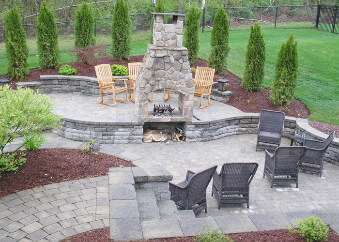 multi-level paver patio with a fireplace and steps by bahler brothers in South Windsor, CT