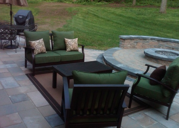 paver patio with a raised fire pit area and a sitting wall by bahler brothers in Connecticut