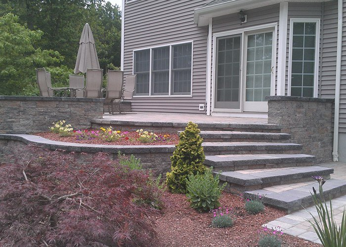raised paver patio in Tolland, CT by bahler brothers includes steps, walls, raised planters, landscaping