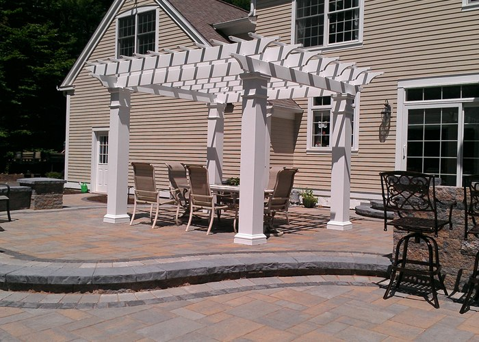 multi-level paver patio in Avon, CT with a built-in outdoor kitchen, pergola, sitting wall, steps and pillars by bahler brothers