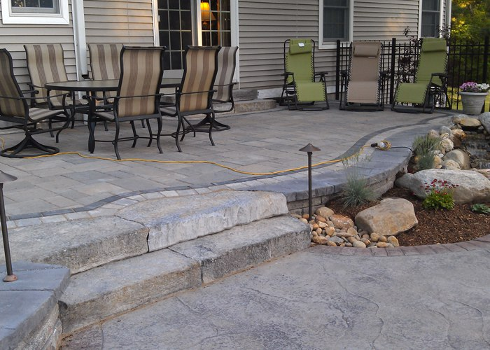 raised paver patio with landscape lighting in Ellington, CT by bahler brothers