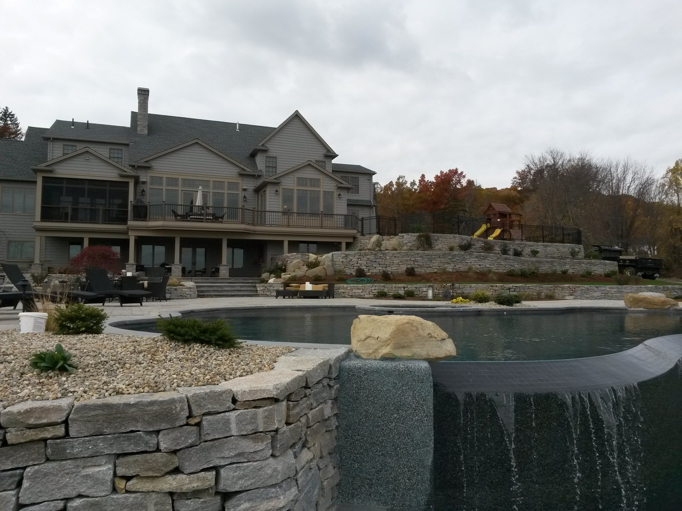 Natural Stone Wall by Bahler Brothers meets infinite edge pool by Aqua Pool in MA