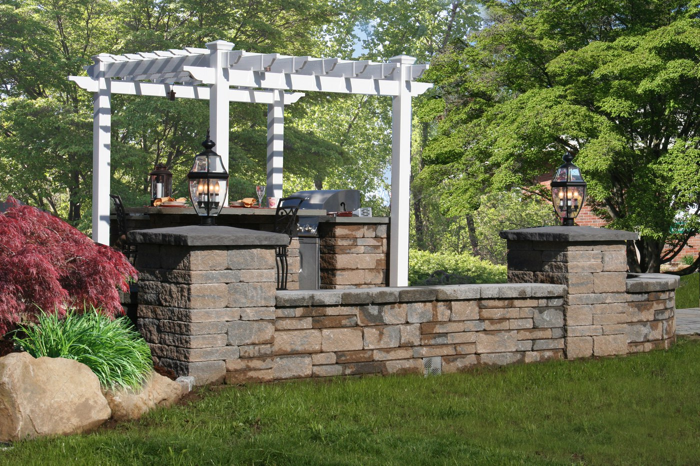 Outdoor Kitchen with Built-in Grill and Pergola by Bahler Brothers in CT