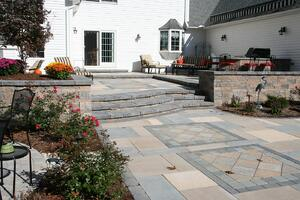 Paver Paver Patio with Retaining Walls and Outdoor Kitchen
