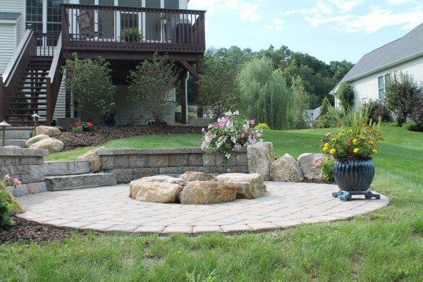 Paver Patio with Fire Pit and Retaining Walls Leading to Deck