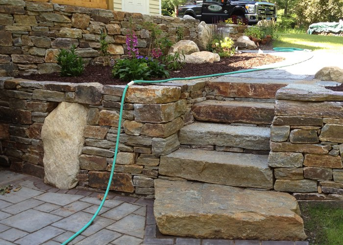 Stone steps and boulders in Stone Retaining Wall in Connecticut. by Bahler Brothers