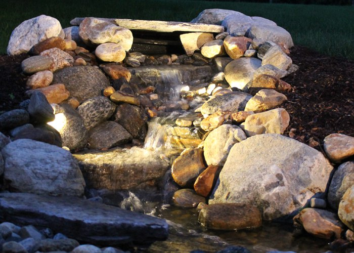 Landscape lighting highlights this pondless water feature in South Windsor, CT. installed by Bahler Brothers.
