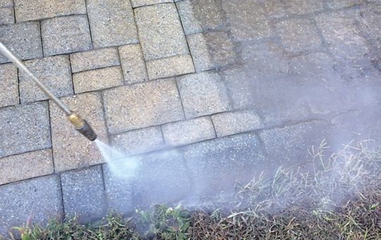 rotating power washer nozzle cleans the paver joints of a patio