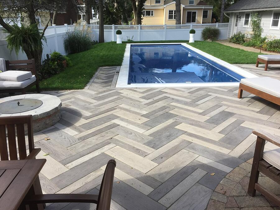 Custom backyard paver patio with pool and fire-pit